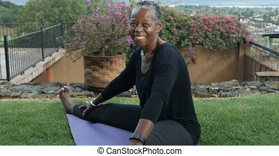 Elderly African American smiling woman stretching her legs sitting on a yoga mat