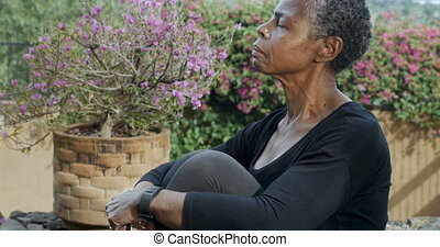 Elderly African American woman straightening her spine and...