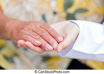 Elderly aid - Young doctor holds the elderly woman hands