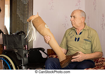 Elderly amputee sitting holding an artificial leg