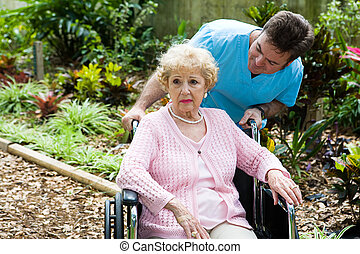 Senior woman in nursing home is feeling depressed and forgotten. Her orderly tries to comfort her.