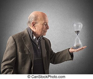 Elderly and the passage of time - Elderly man holds an...