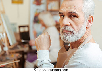 Elderly artist posing in painting class