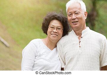Elderly Asian couple smiling outdoor.