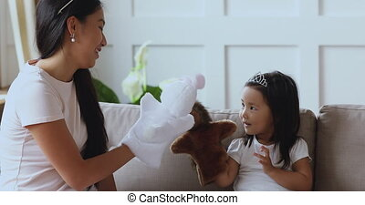 Elderly asian ethnicity sister playing hand toys with cute girl.