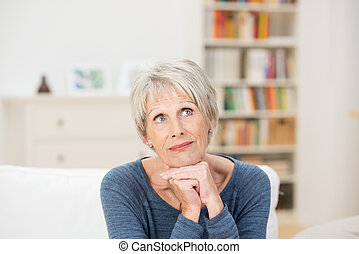 Elderly attractive woman sitting reminiscing
