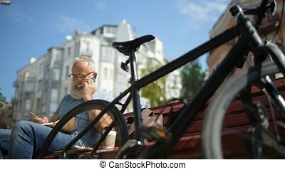 Elderly bearded guy smiling while having phone talk outdoors...