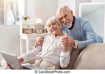 Elderly beautiful couple watching photos at the laptop