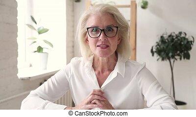 Elderly blond woman teacher makes video call chatting online...