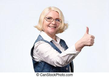 Elderly blonde european woman giving a thumb up