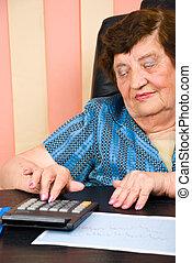 Elderly business woman calculating