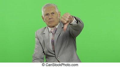 Elderly businessman giving thumb dow. Old man in formal wear...
