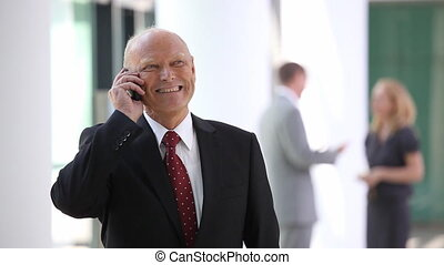 elderly businessman on the phone with blurred team