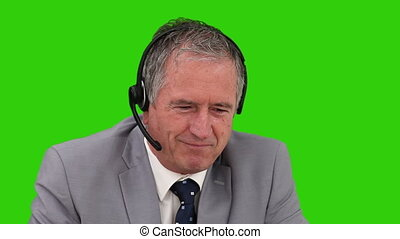 Elderly businessman speaking over the headset