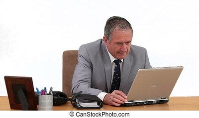 Elderly businessman working on his laptop
