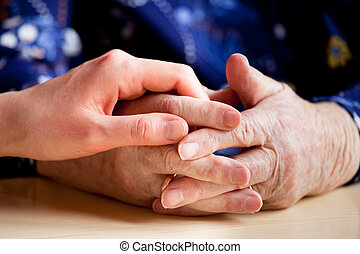 Elderly Care - A young hand holding an elderly pair of hands