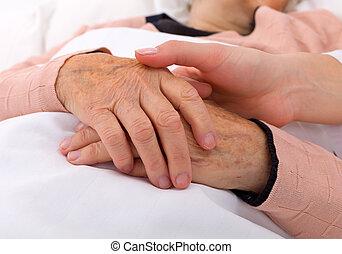 Elderly care - Caregiver holding elderly patients hand at...