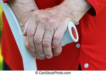 Elderly care - Elderly wrinkled hands holding a crutch
