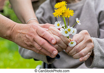 Elderly care - hands, bouquet