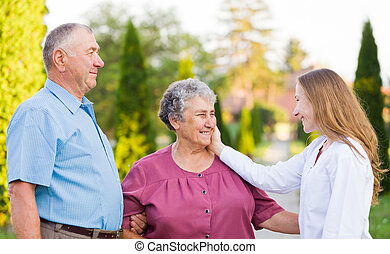 Happy elderly couple with their carer in the nature