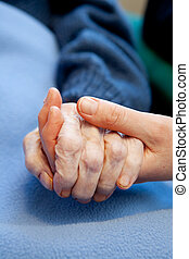 Elderly Care - A young hand touches and holds an old...