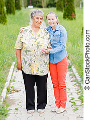 Elderly care - Elderly woman walk with her daughter in the...