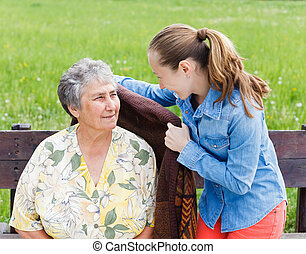 Elderly care - Young girl wrap her mother with a warm...