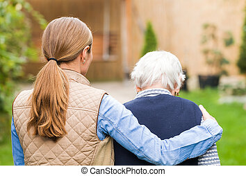 Elderly care - Young carer walking with the elderly woman in...