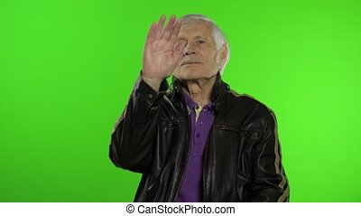 Elderly stylish grandfather caucasian rocker and biker mature man waves his hands, greets on chroma key background. Old senior grandparent in fashion leather jacket. Green screen