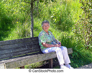 elderly Caucasian woman on park bench