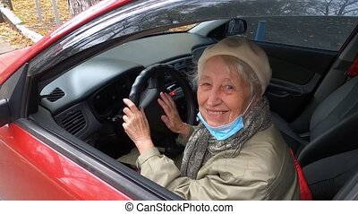 Elderly caucasian woman with her facemask in the car. Female senior citizen in mask to protect herself from the COVID19 virus.