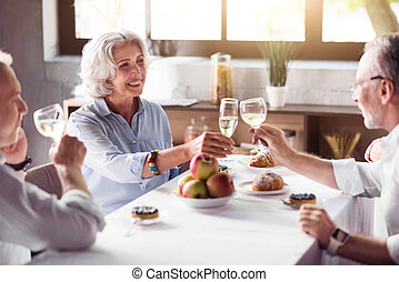 Elderly ceerful woman drinking with her family