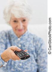 Elderly cheerful woman using the remote