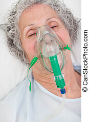 Elderly closing her eyes while lying in a hospital bed