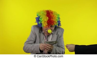 Senior clown manager office worker in wig and business suit receive money cash for dancing, entertains, celebrate, making silly faces. Guy businessman entrepreneur boss at work. Yellow background
