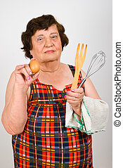 Elderly cook woman showing egg