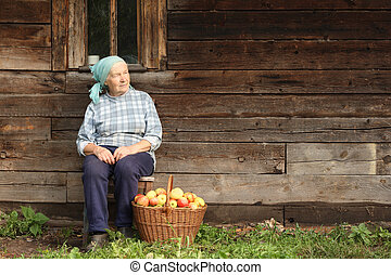 Elderly countrywoman - Senior countrywoman sitting against...
