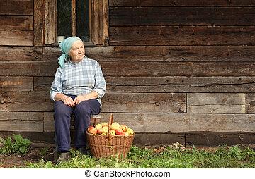 Elderly countrywoman - Senior countrywoman sitting against...