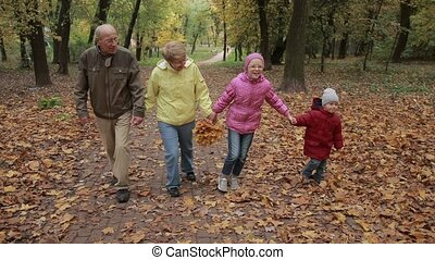 Elderly couple and grandchildren together in autumn -...