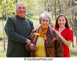 Elderly couple and young caregiver - Photo of happy elderly...