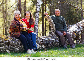 Elderly couple and young caregiver sitting on tree trunk in...