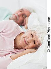 Elderly couple asleep in bed