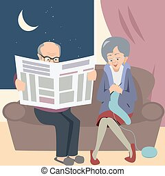 elderly couple at night in home knitting and reading