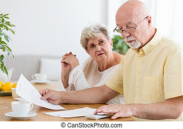 Elderly couple calculating costs of household. Senior people with low pension
