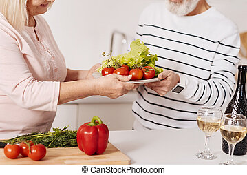 Elderly couple cooking dinner together in the kitchen