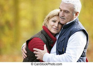 Elderly couple cuddling in park