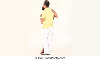 Elderly couple dancing againsta white background