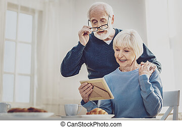 Delighted aged man holding his glasses