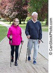 Elderly couple doing nordic walking - Photo of elderly...