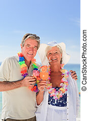 Elderly couple drinking a cocktail on the beach